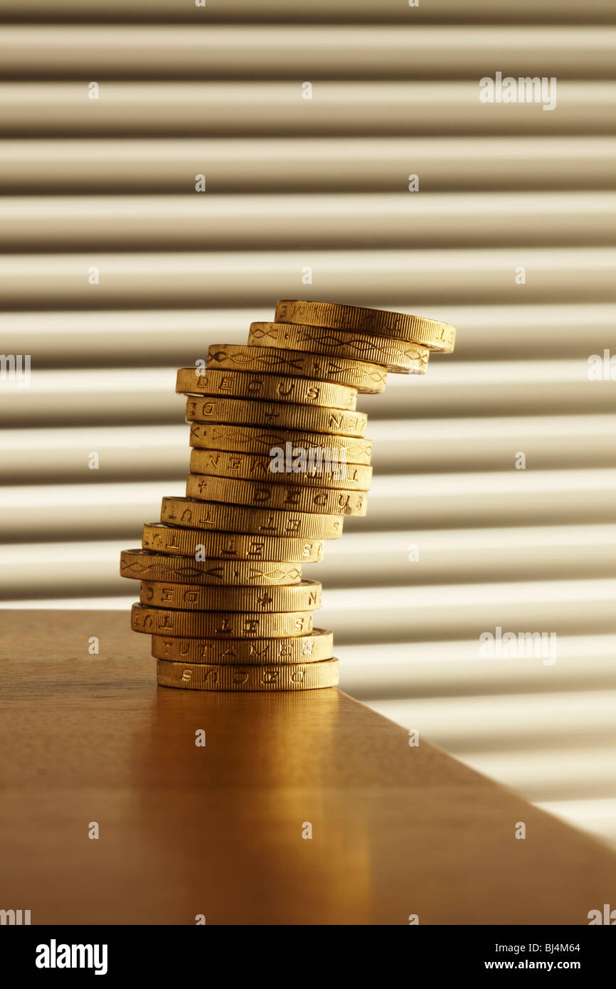 Libra la pila de monedas en el borde de la tabla Imagen De Stock