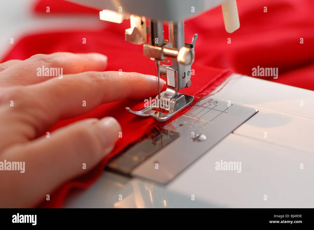Una mano de una costurera apoyando un paño mientras la costura a máquina de coser. Foto de stock