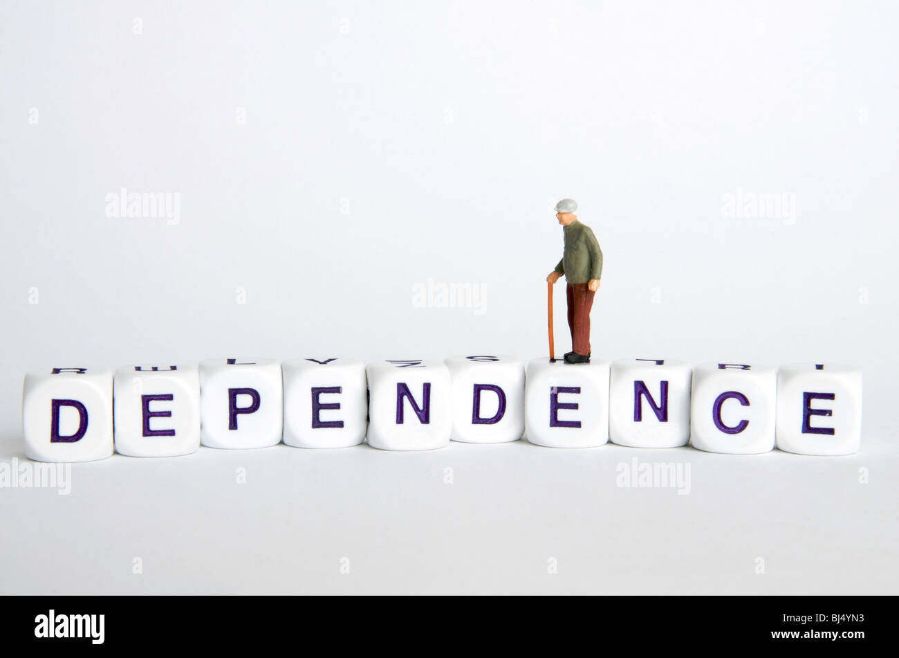 """Ancianos dependencia / independencia - viejo concepto figura de pie en la palabra """"dependencia"""". Imagen De Stock"""