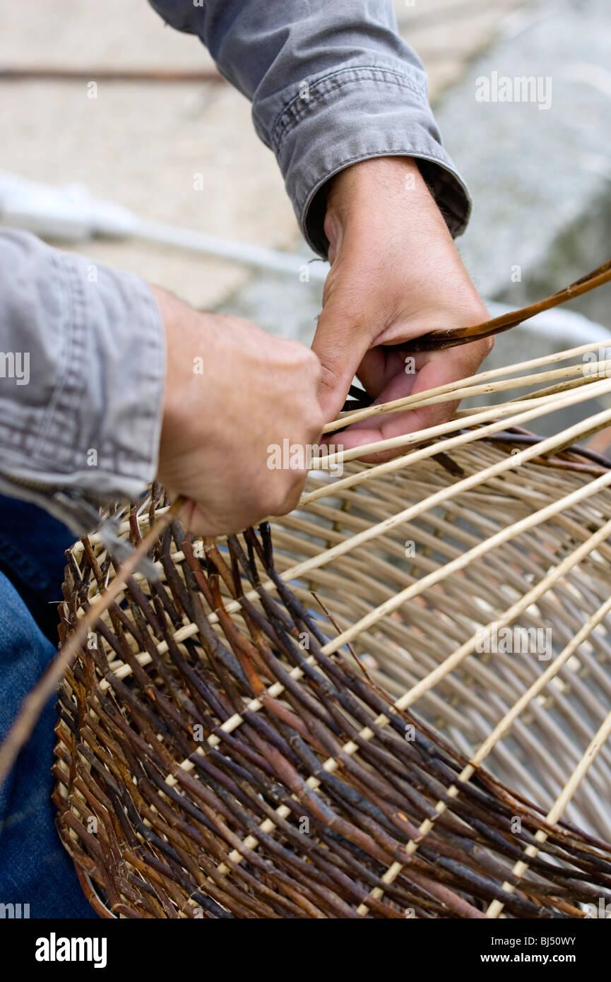 Una cesta weaver sentado en la calle y el tejer una cesta, Bretaña, Francia, Europa Imagen De Stock