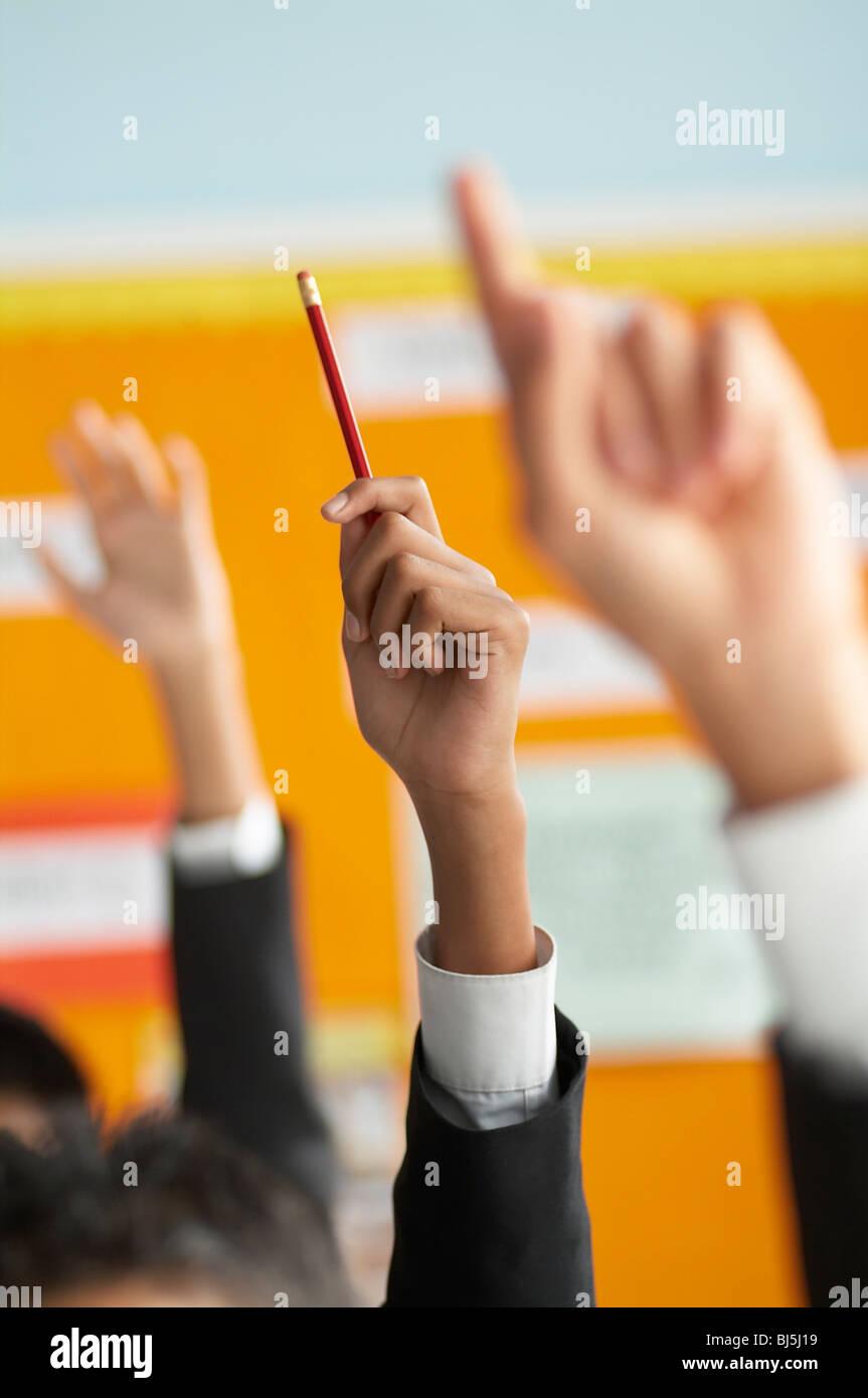 Aula escolar, manos, manos arriba, lápiz luminoso, educación, aprendizaje, respuesta, diverso Imagen De Stock
