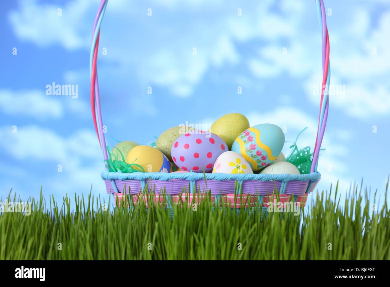 Canasta de Pascua en la hierba con el cielo azul Foto de stock