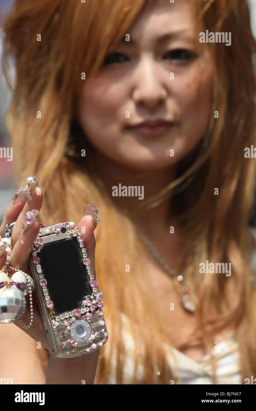 El uso del teléfono móvil japonés por viajeros y público en Tokio, Japón, en 2007. Imagen De Stock