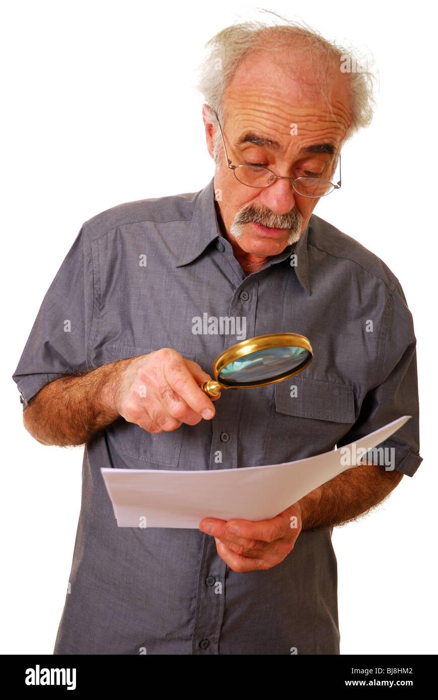 Anciano con lupa para leer Foto de stock