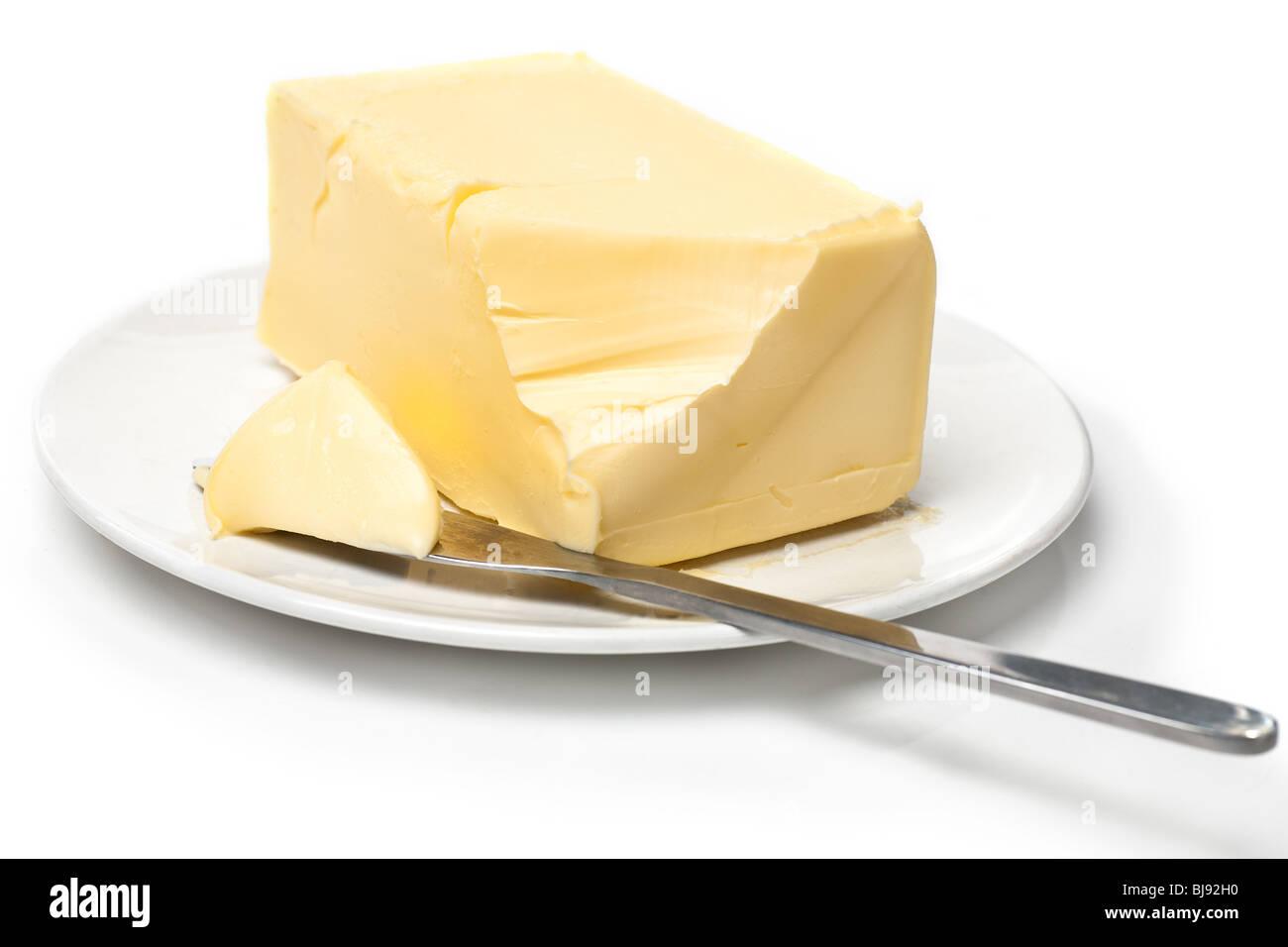 Trozo de mantequilla en la placa blanca con cuchillo. Fondo blanco y poca atención. Imagen De Stock