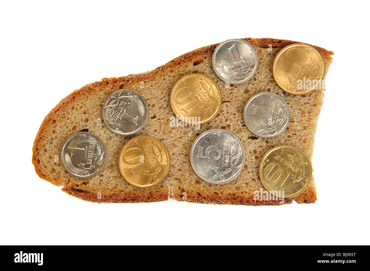 Monedas sobre pan de centeno slice. Aislado sobre blanco Imagen De Stock