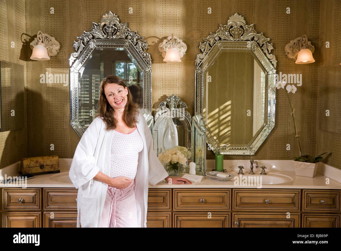 19c74dcfe4dd Mujer embarazada por tocador de baño permanente en pijama Foto ...