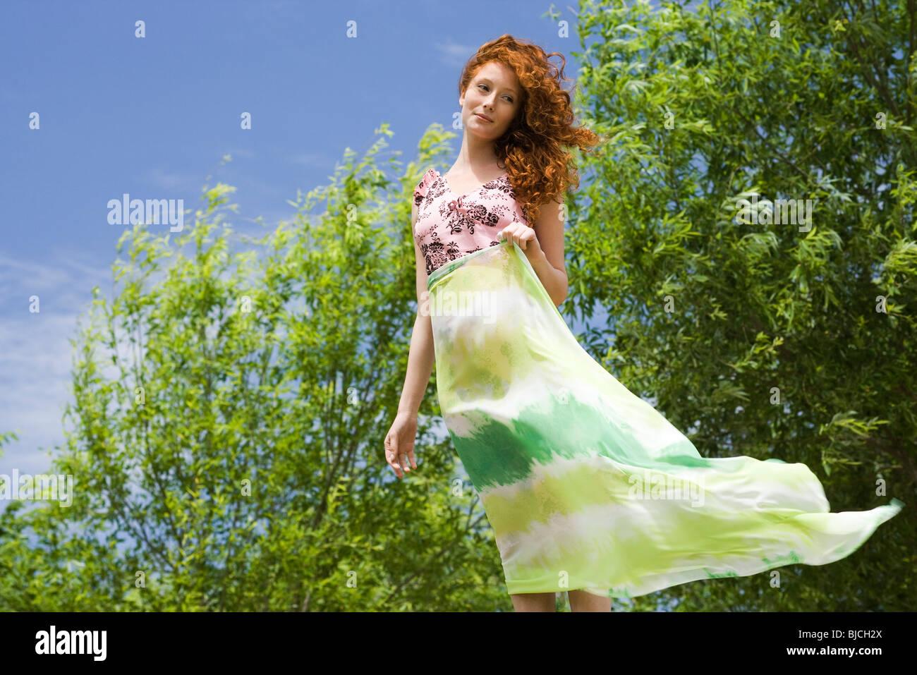 Mujer joven de pie en el exterior, sosteniendo la bufanda en el viento Foto de stock