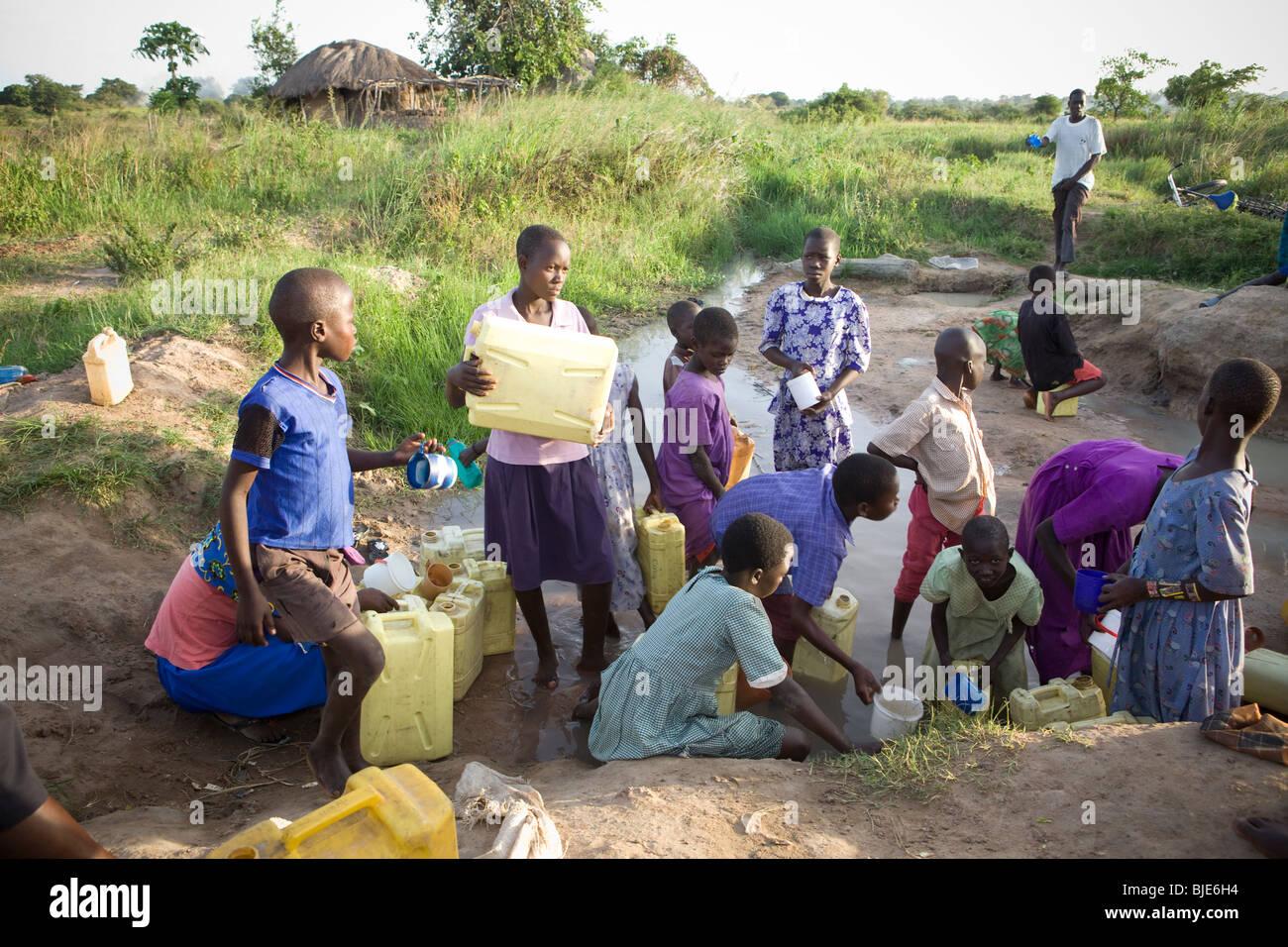Los niños extraen agua de un abrevadero, en el distrito de Amuria, Uganda, África Oriental. Foto de stock