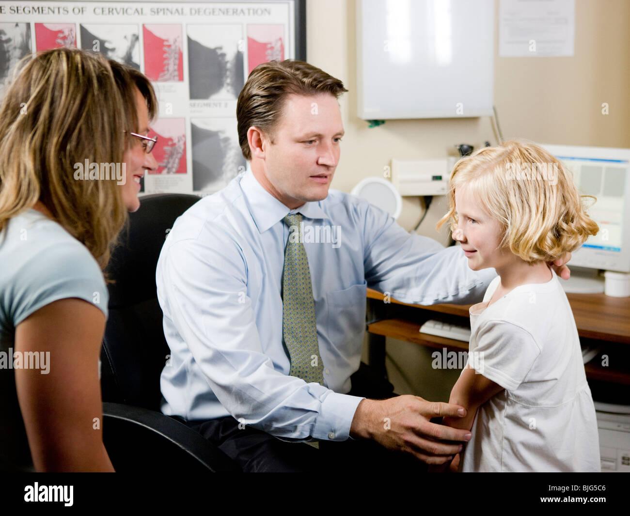 Chica y su madre en la consulta del quiropráctico Imagen De Stock
