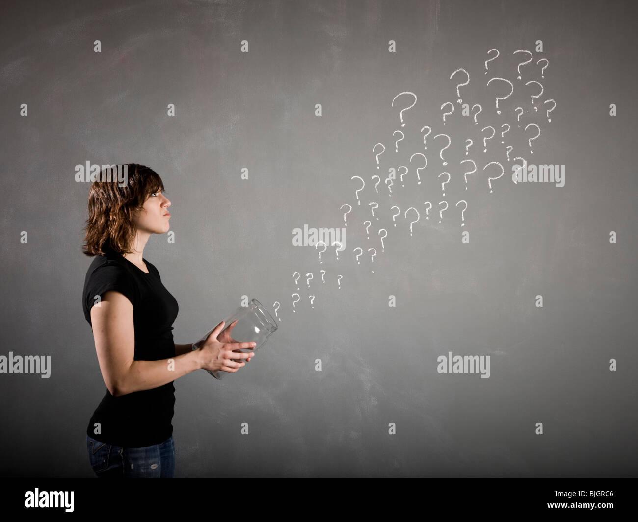 Mujer con una jarra llena de signos de interrogación Foto de stock