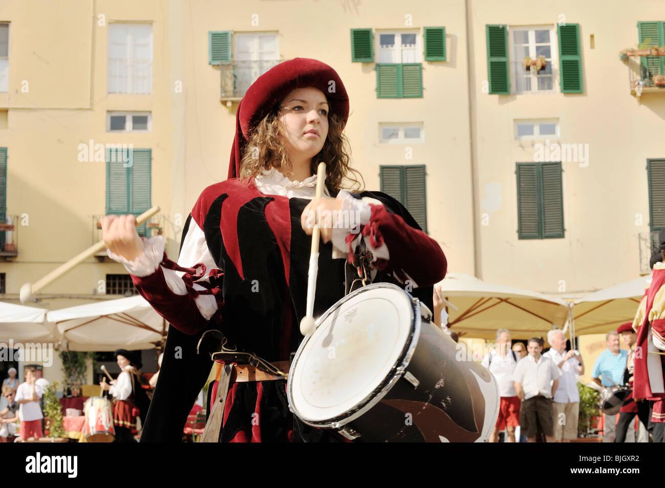 La ciudad italiana de Lucca. Mujer joven baterista en traje medieval street festival Pageant. Toscana, Italia Imagen De Stock