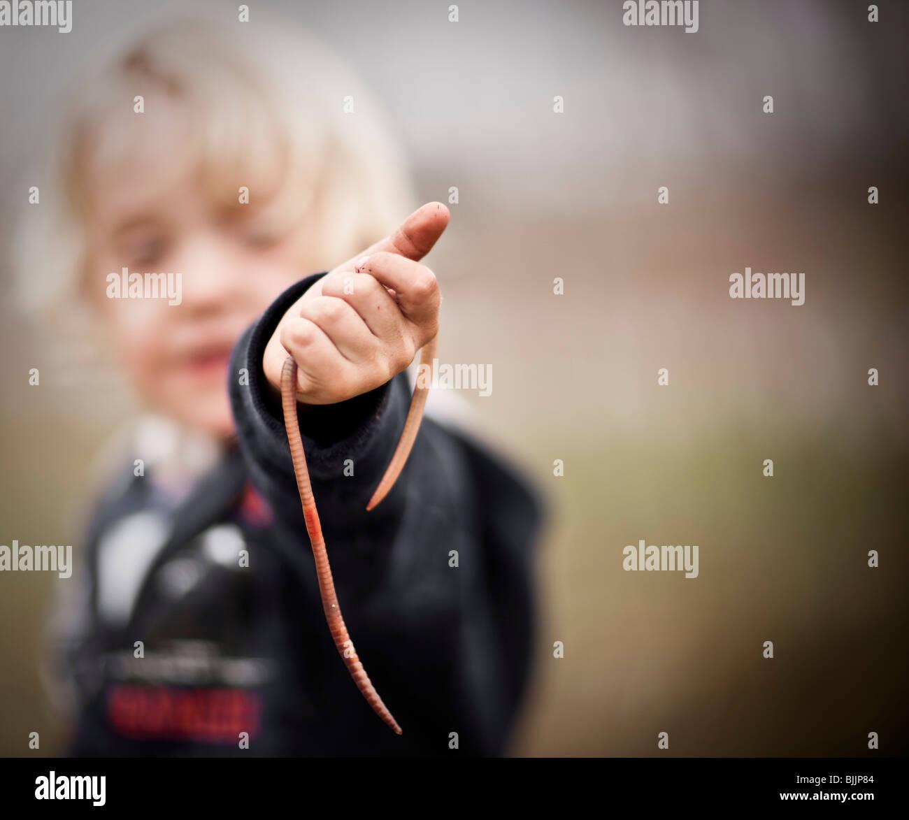 Joven sostiene un gusano. Imagen De Stock