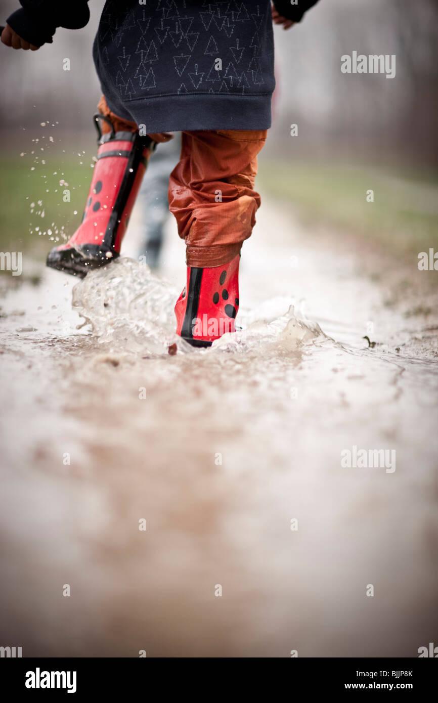 Joven llevaba botas de agua, camina a través de un charco de agua. Imagen De Stock
