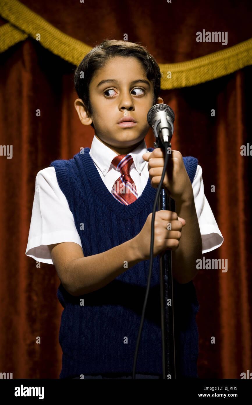 Chico de pie en el escenario con micrófono y grandes ojos Foto de stock