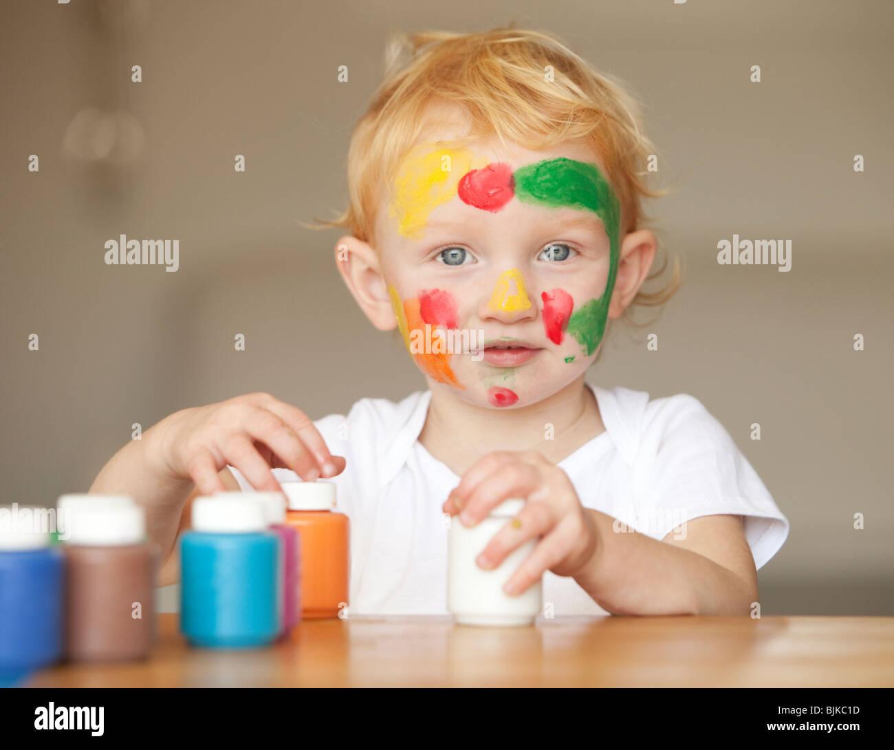 Niña jugando con pintura del dedo Imagen De Stock