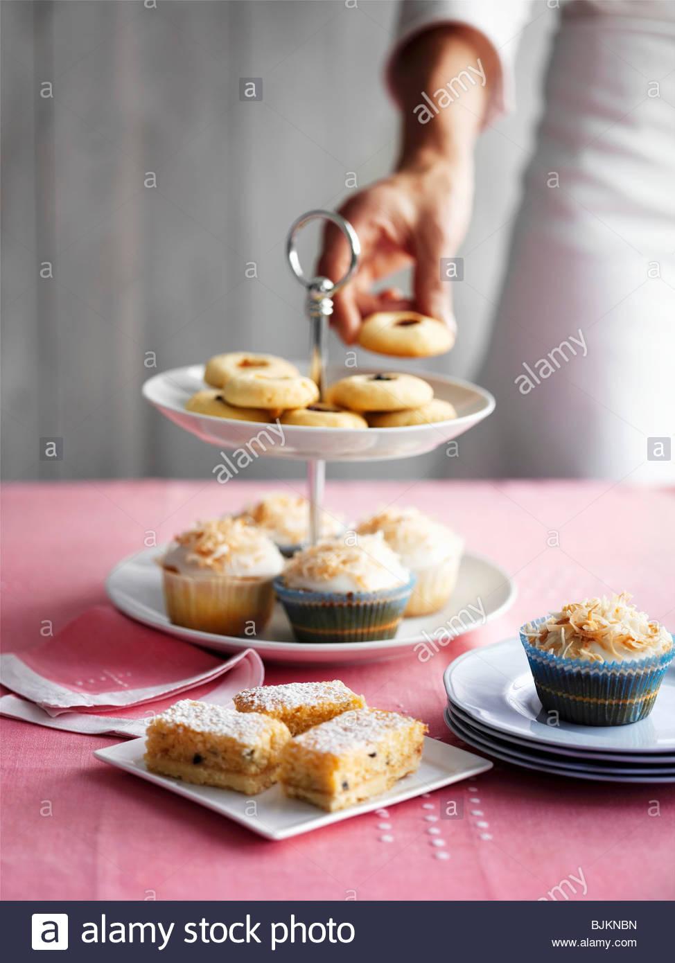 Bollos y pasteles pequeños de tiered stand Imagen De Stock