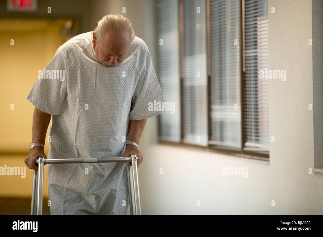 Hombre maduro en bata de hospital con walker Imagen De Stock