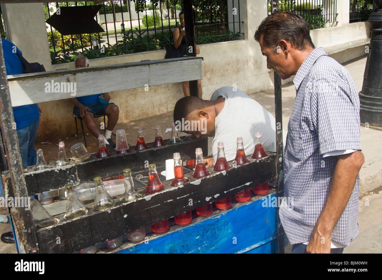 Un Cubano adquirir un refresco azucarado fuera un vendedor callejero en La Habana esta bebida no es recomendable Imagen De Stock