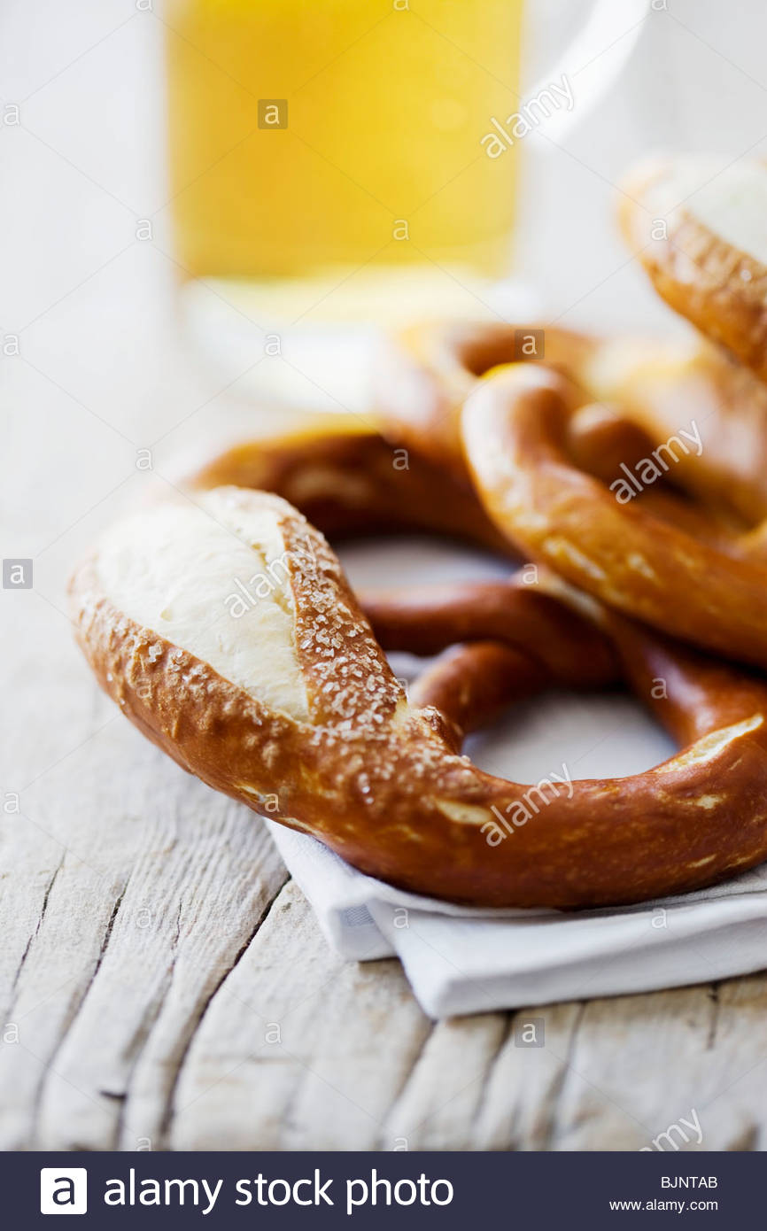 Varios pretzels suaves y vaso de cerveza Imagen De Stock