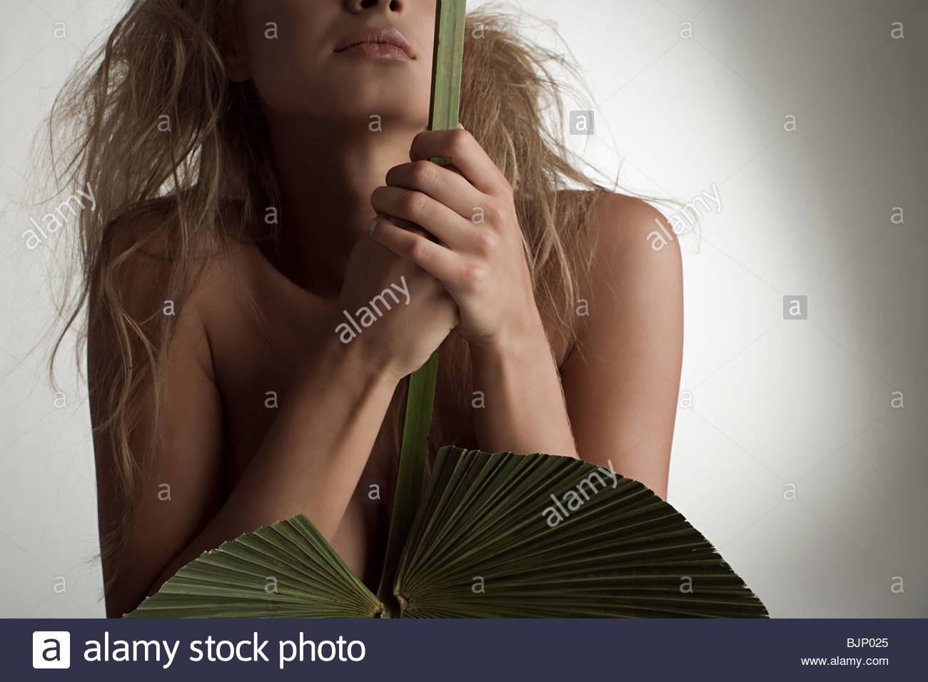 Una joven mujer sosteniendo una hoja de palma Imagen De Stock