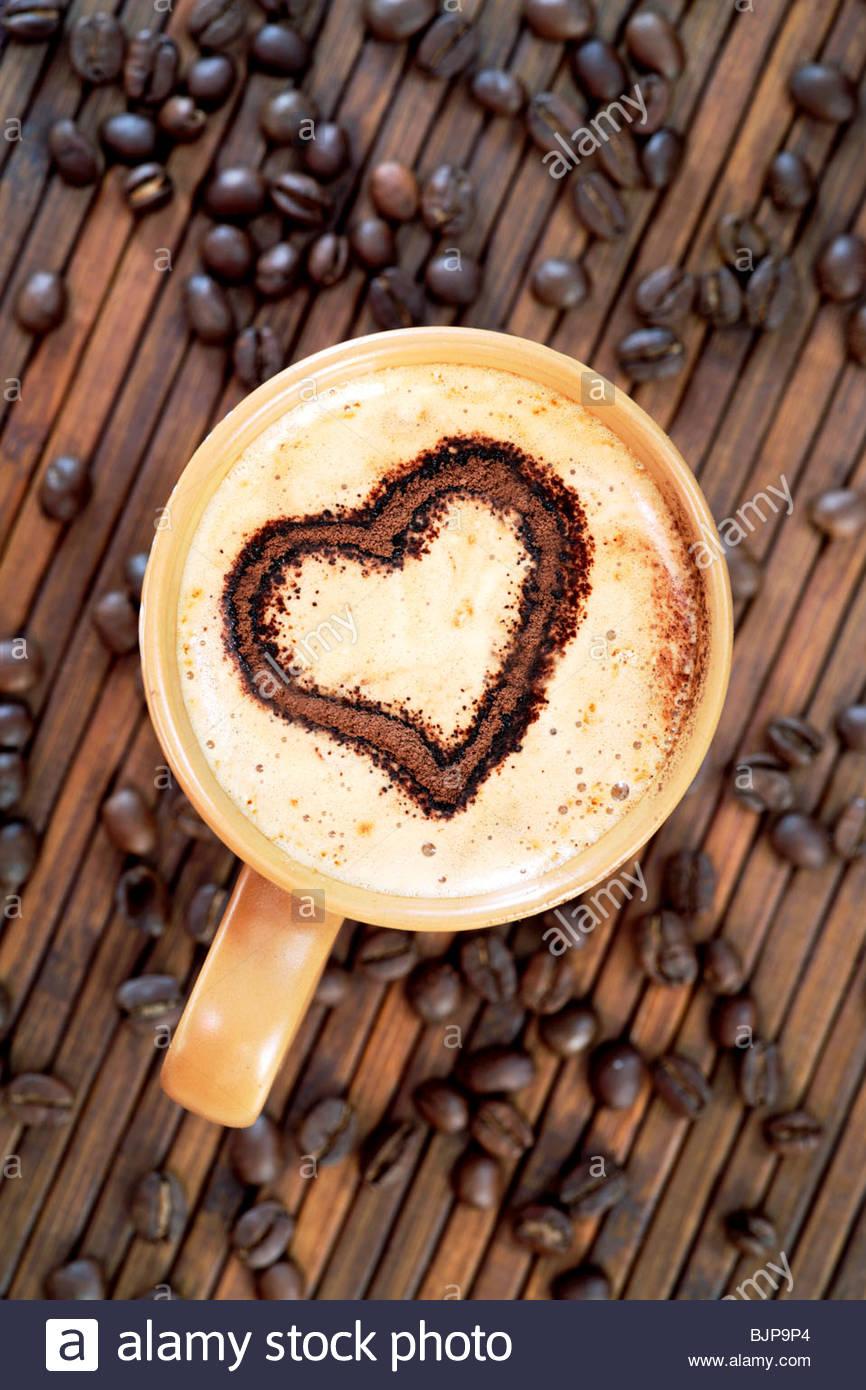Decoración en corazón capuchino con espuma de leche y granos de café. Imagen De Stock