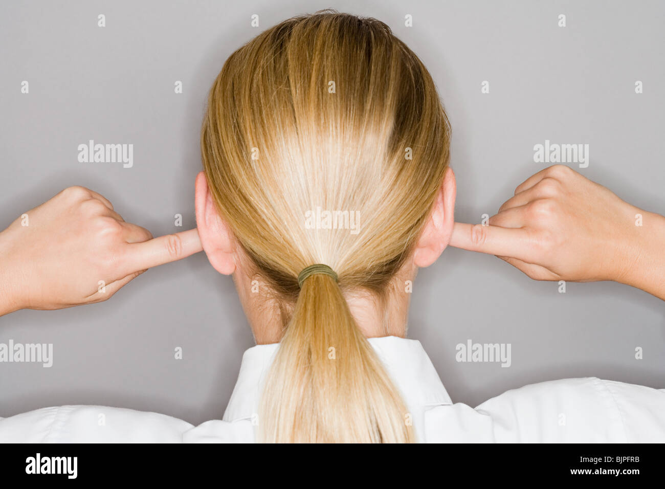 Una mujer con sus dedos en su oído Imagen De Stock