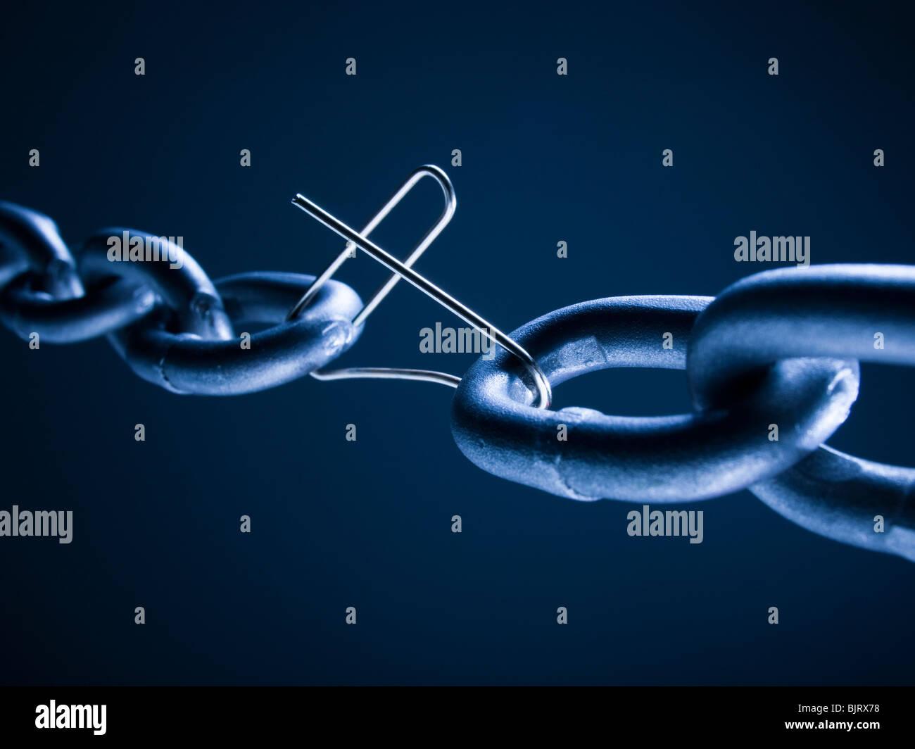 Cadena vinculada con clip roto contra el fondo azul. Imagen De Stock