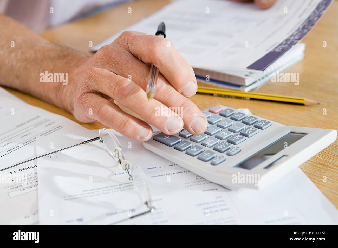 Una persona con una calculadora. Imagen De Stock