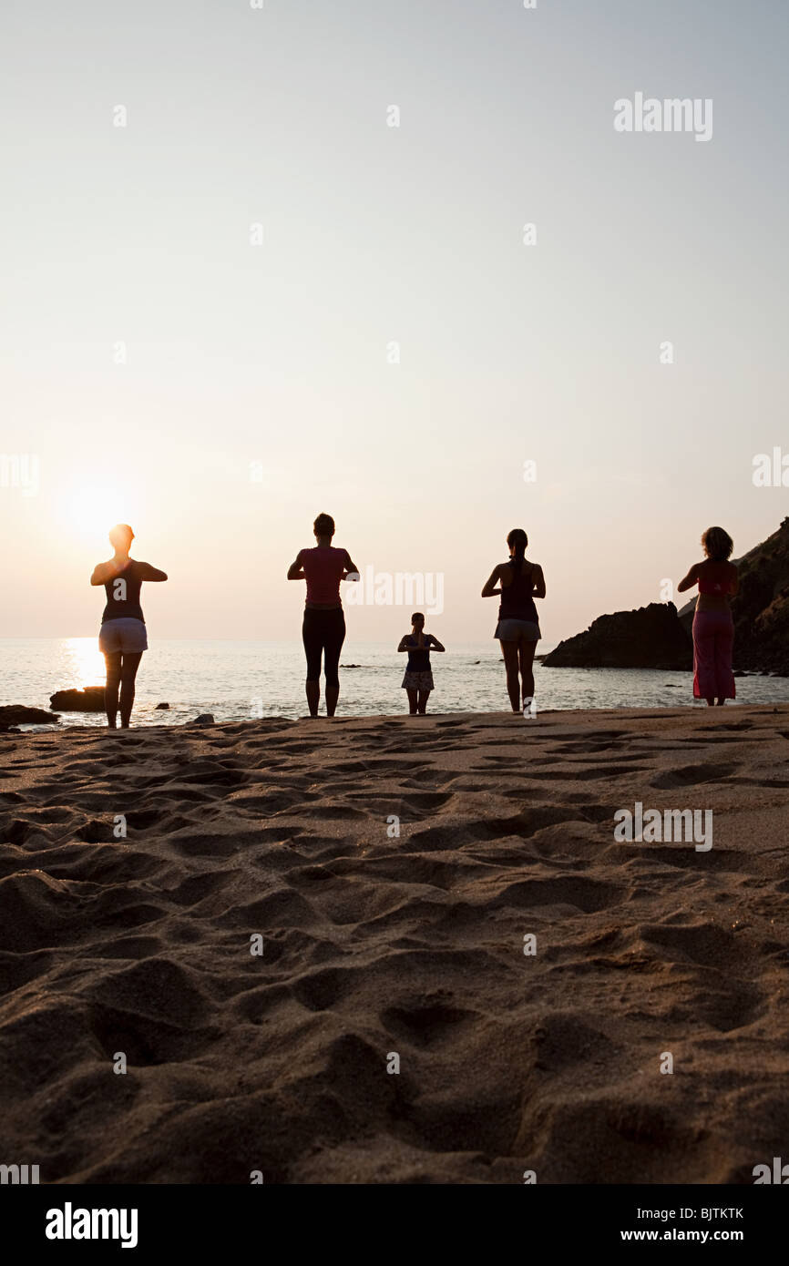 Las mujeres que practican yoga en la playa en el atardecer. Imagen De Stock