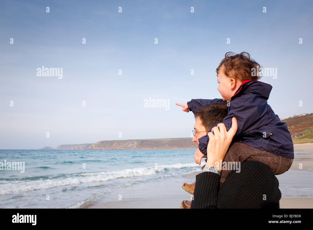 El hombre con el niño sobre los hombros mirando a ver. Niño apuntando. Imagen De Stock