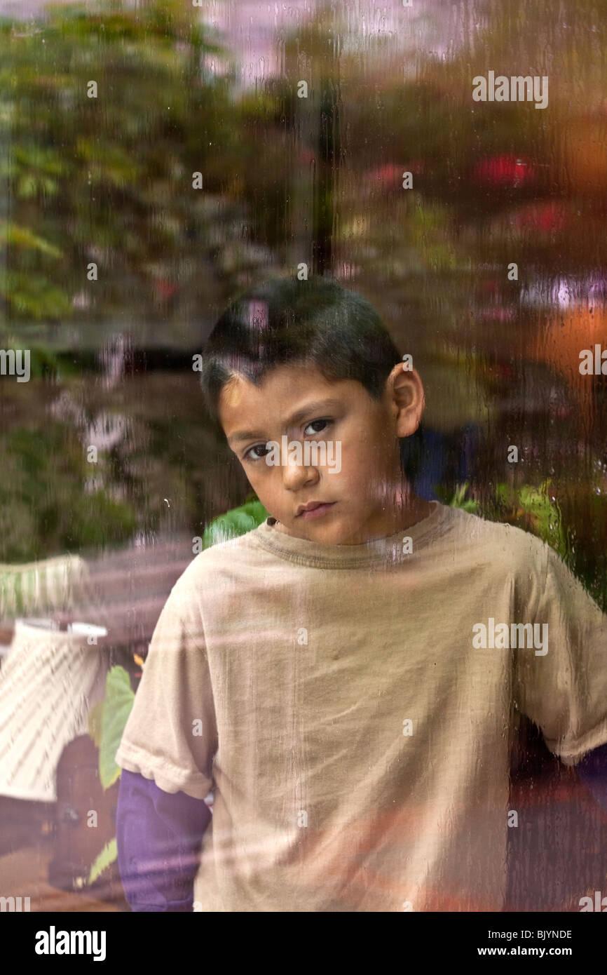 Multi-cultural multicultural 9 -10 años viejo muchacho mirando a través de una ventana en un día Imagen De Stock