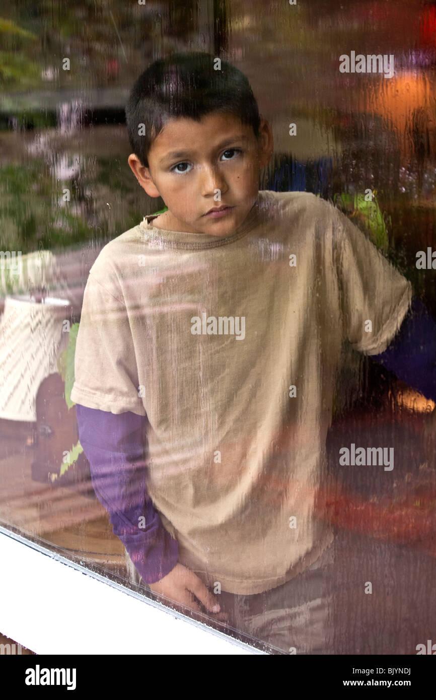 Multi-cultural multicultural 9 -10 años viejo niño hispano mirando a través de una ventana en un Imagen De Stock