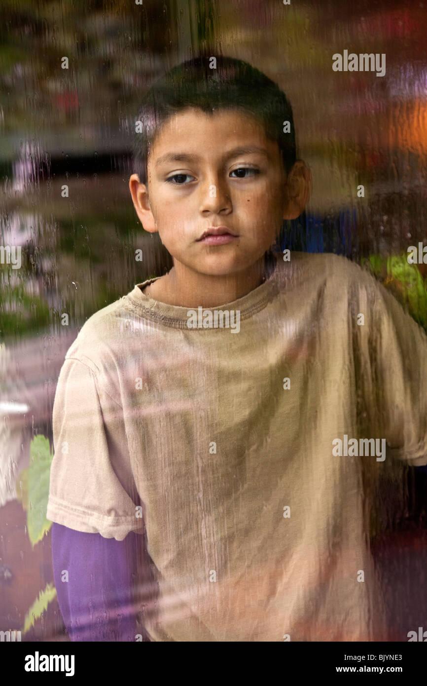 Multi-cultural multicultural niño 9 -10 años viejo niño hispano mirando a través de una ventana Imagen De Stock