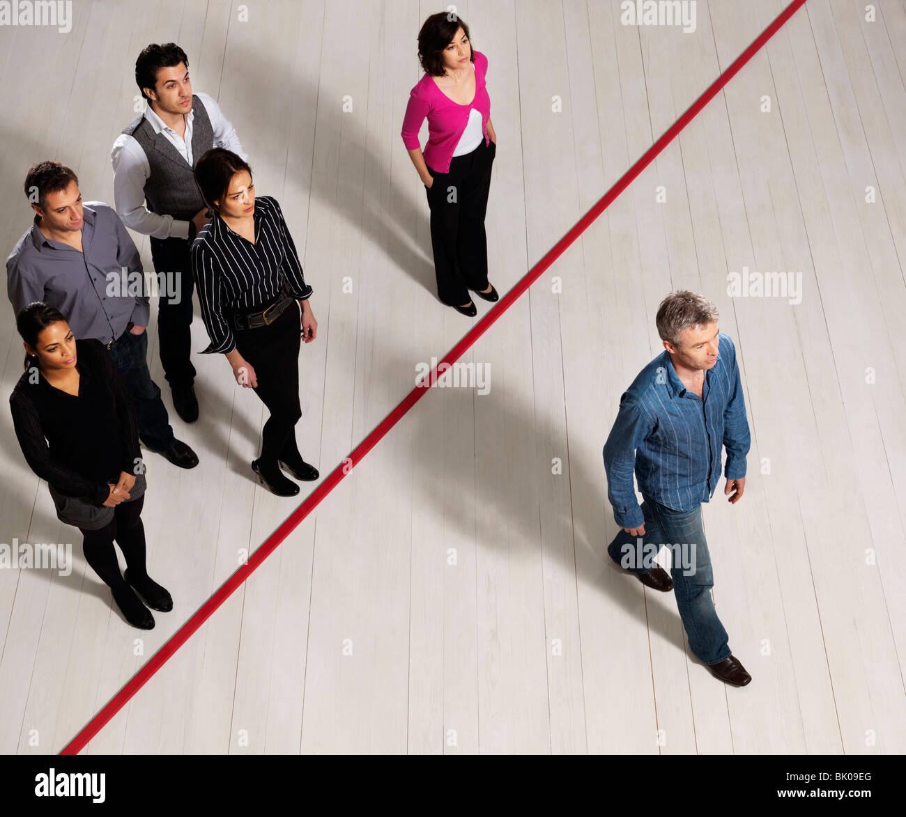 Los hombres y mujeres de negocios cruzando la línea roja Imagen De Stock