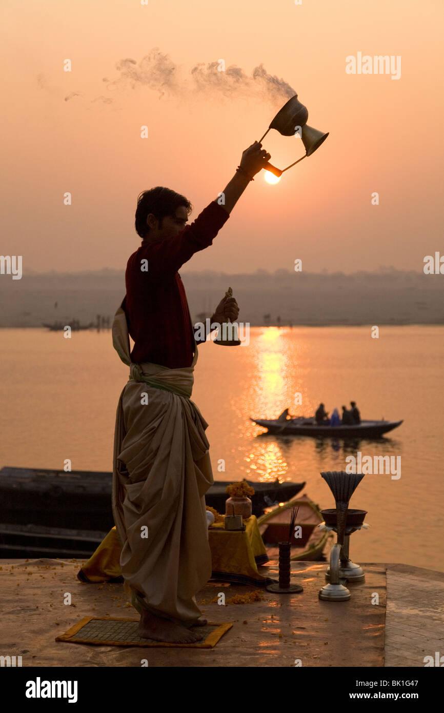 Un sacerdote Hindú realiza diariamente la Ganga Aarthi ritual por las orillas del río Ganga (Ganges) en Imagen De Stock