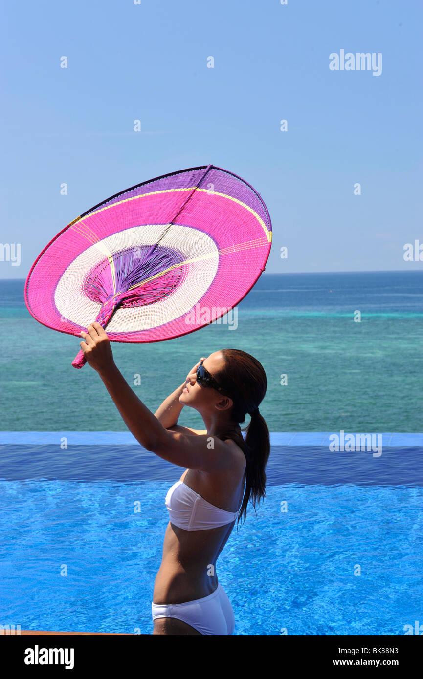 Chica con un ventilador en la piscina en el Eskaya Beach Resort y Spa, Bohol, Filipinas, el sudeste de Asia, Asia Imagen De Stock