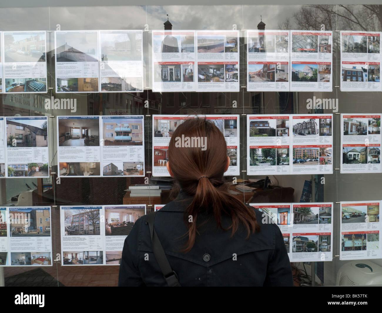 Mujer mirando casas en venta en agentes inmobiliarios ventana en Utrecht, los Países Bajos Imagen De Stock