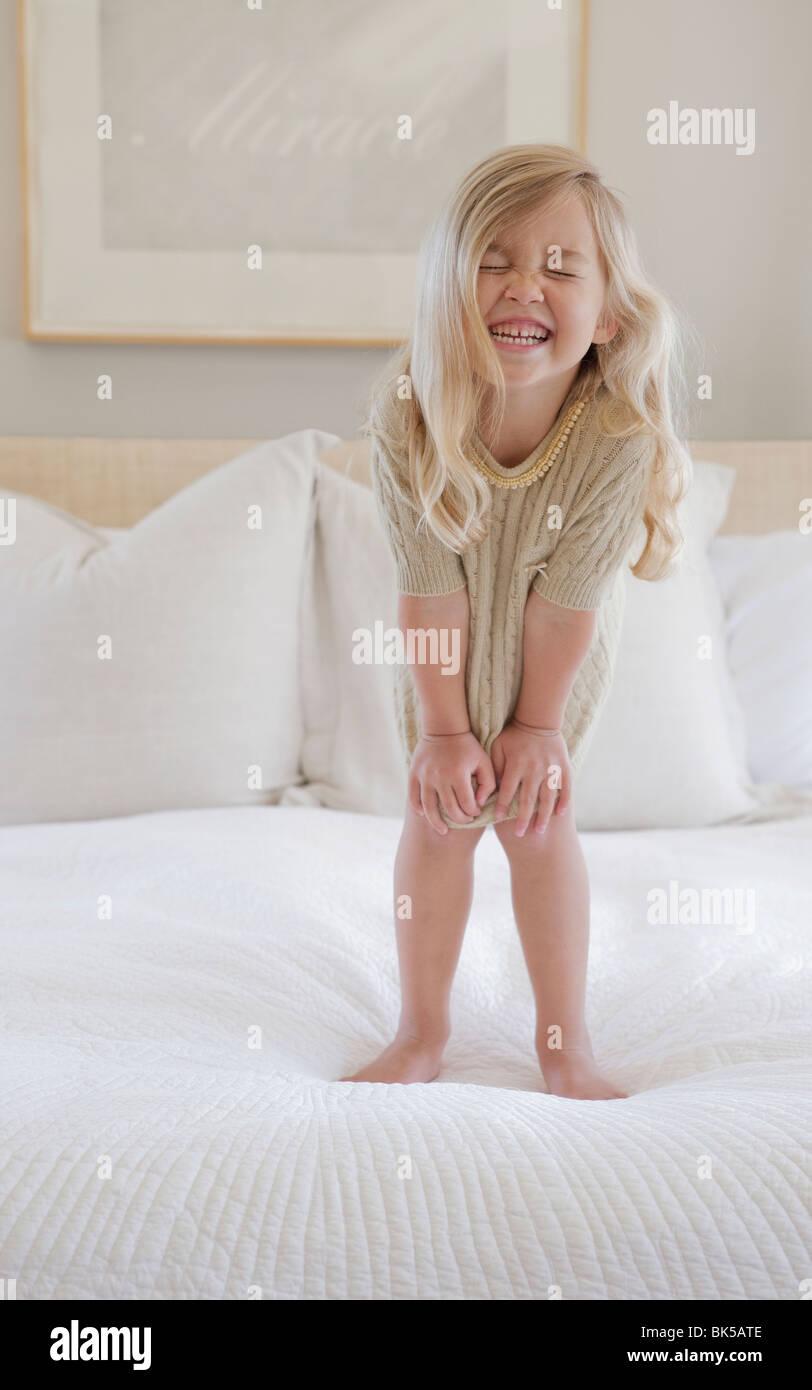 Chica con gran sonrisa de pie en la cama Imagen De Stock