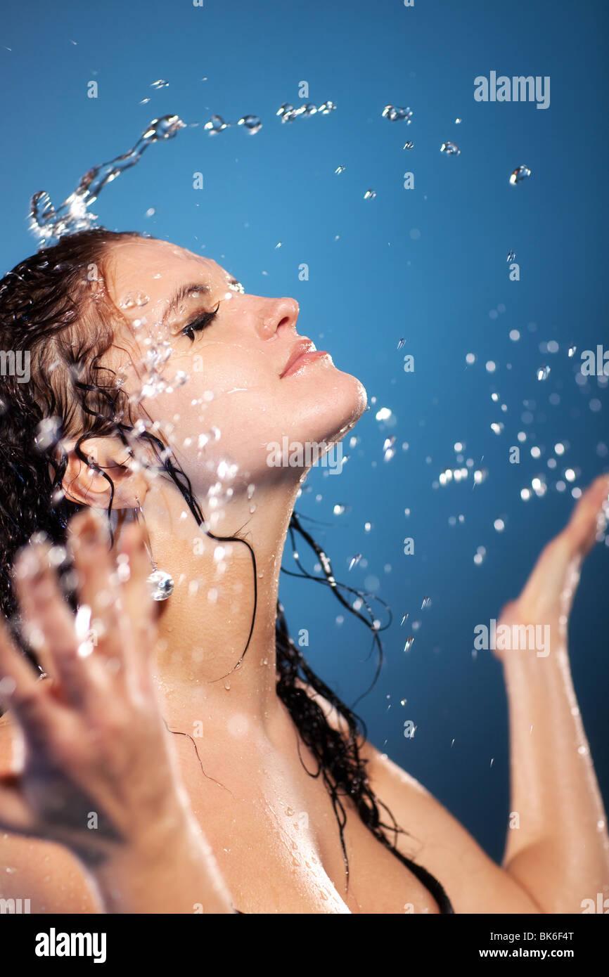 Mujer joven lavándose la cara. Sobre fondo azul. Imagen De Stock