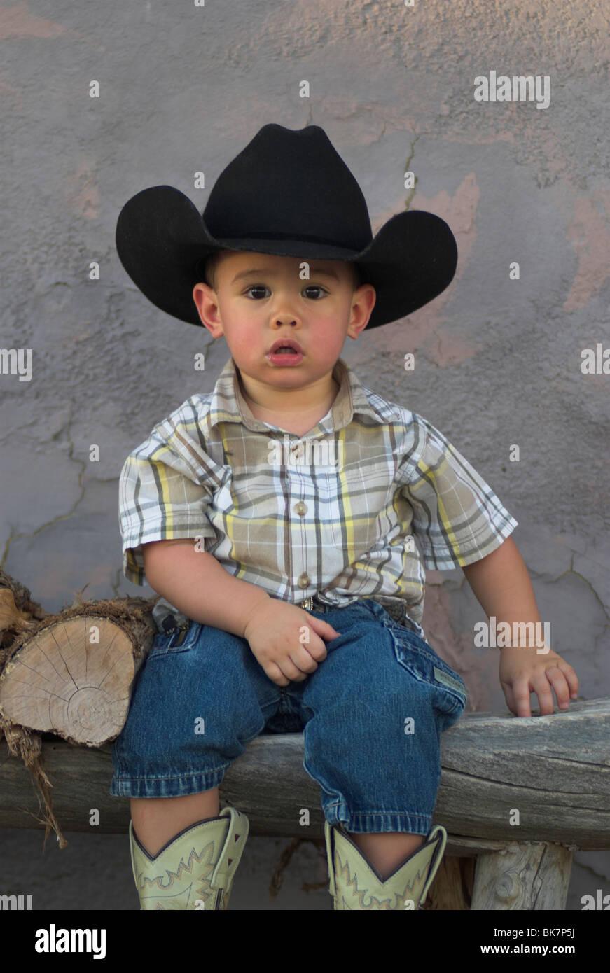 Un lindo 2-4 años de raza mixta niño usando un sombrero de vaquero y  sentado en un banco(liberado) 177596f0f9bb