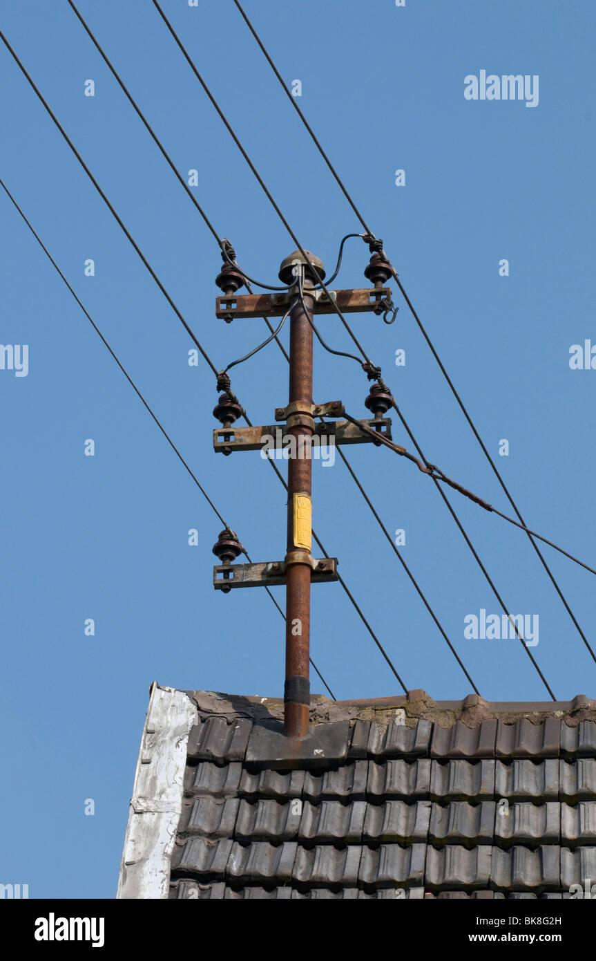 Antiguas líneas aéreas de energía doméstica con aislantes cerámicos en el techo Foto de stock