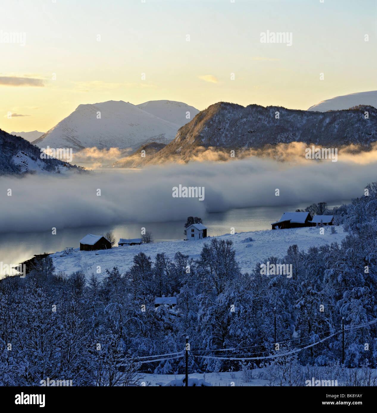 Niebla, hielo, humo sobre un fiordo en el norte de Noruega, un frío día de invierno. Foto de stock