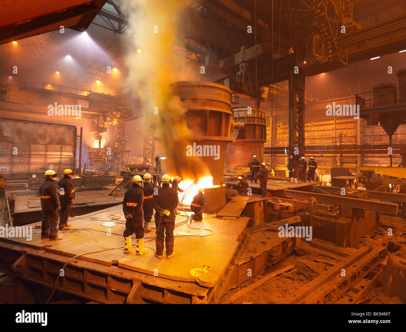 Los trabajadores siderúrgicos en la planta trabajan en cucharón Foto de stock