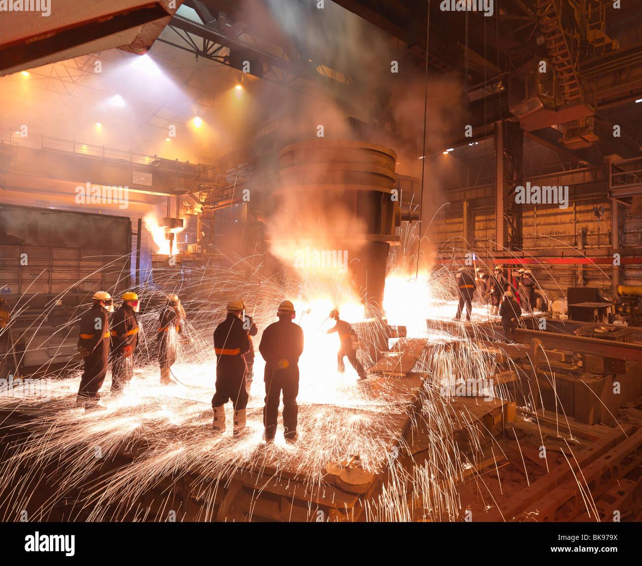 Los trabajadores con acero fundido en la planta Foto de stock