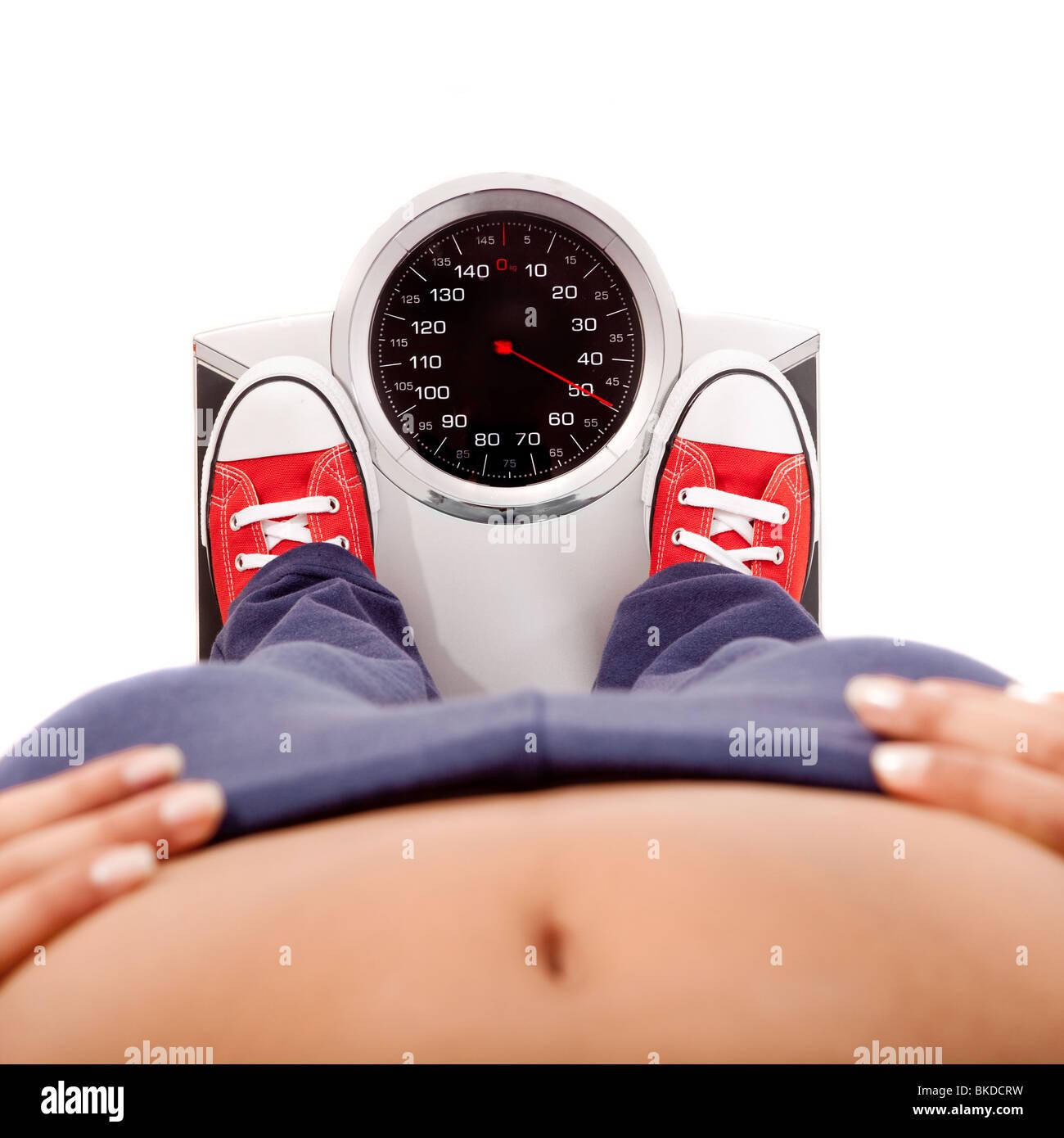 Joven atlético midiendo su peso con una balanza Imagen De Stock