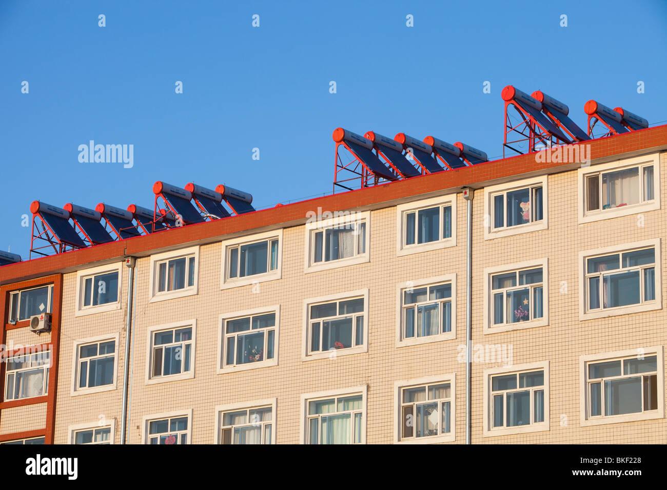 Nuevos apartamentos en chino con los calentadores de agua solares en el tejado. Imagen De Stock