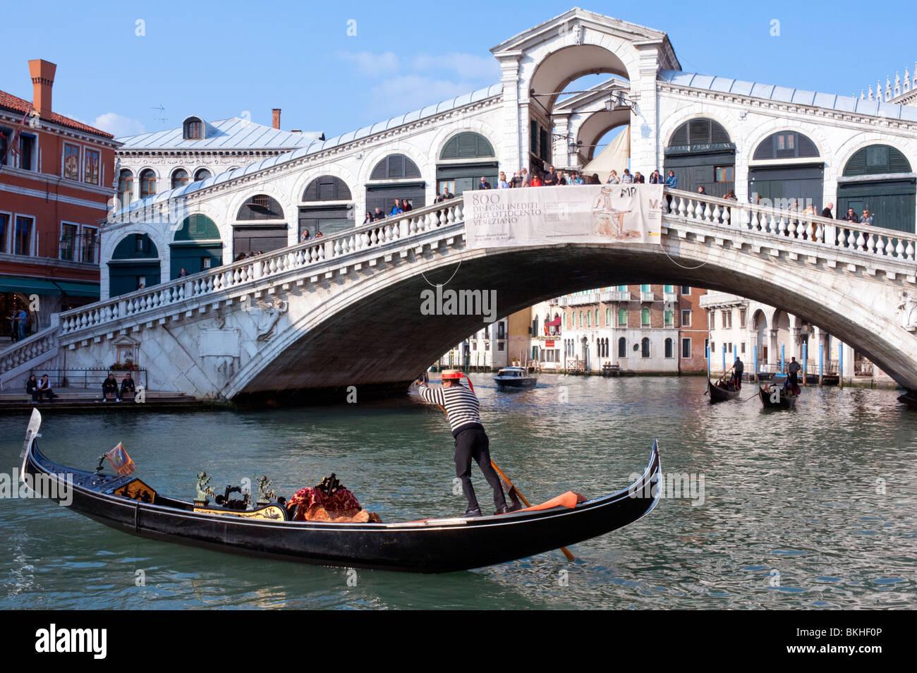 Gondolero y su góndola por el Gran Canal, el Puente de Rialto en Venecia Italia Imagen De Stock