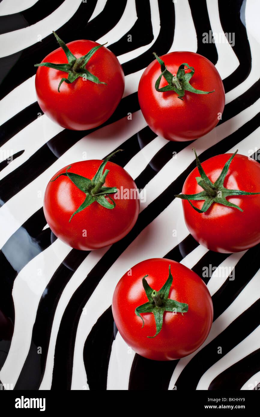 Cinco tomates en placa de rayas Imagen De Stock