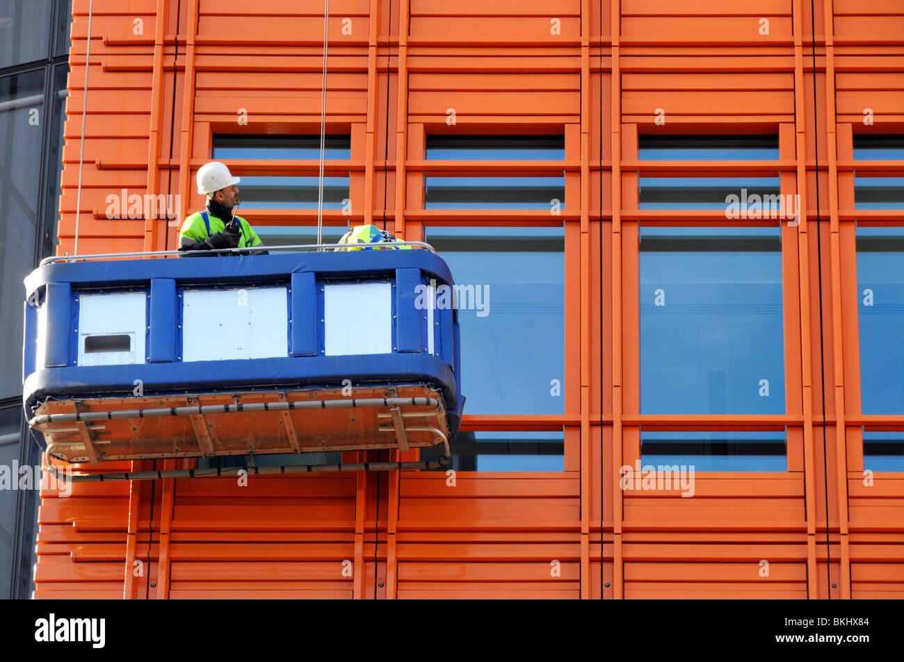 Hombre en cuna de inspeccionar el revestimiento en el nuevo edificio alto Imagen De Stock